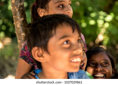Siblings in a small village smiling in India