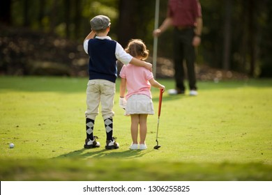 Siblings with their arms around each other on golf course
