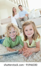 Siblings together on the carpet with tablet and parents behind them