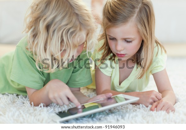 Siblings together on the floor using tablet