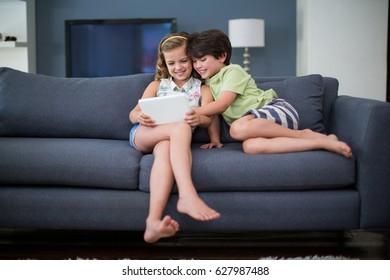 Siblings using digital tablet in living room at home