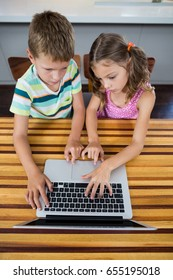Siblings using laptop in kitchen at home