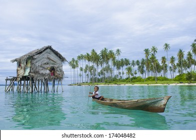 SIBUAN ISLAND, SABAH, MALAYSIA - JANUARY 29 : Unidentified Sea Gypsies boy paddles a boat on January 29, 2012 in Sabah, Malaysia. The Sea Gypsies are sea nomads that move from one place to another.