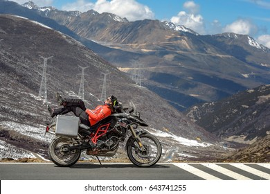 Sichuan, China - April 13, 2017:Asian girl from Thailand  relaxing on her motorcycle in a snow mountain the local people call Shambhala in Sichuan,China.