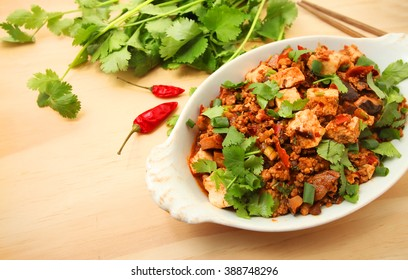 sichuan mapo tofu, chinese food over wooden table background with copy space