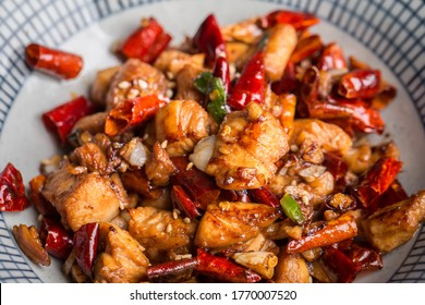 sichuan traditional dishes.chicken cubes with chili peppers on wood table.