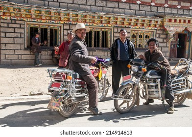 Sichuan,China - October 20,2008 :  An unidentified tibetan  Chinese people with motorcycle at the country town of Daocheng, Sichuan Province, China.Tibetan people are an ethnic group native to Tibet.