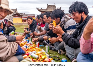 Sichuan/China-08.04.2020:People celebrating the holy festival in small remote buddhist monastery, sitting and eating food in traditional tibetan dress