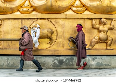 Sichuan/China-08.04.2020:People rolling the big golden rolling prayer drum in the tibetan buddhist monastery