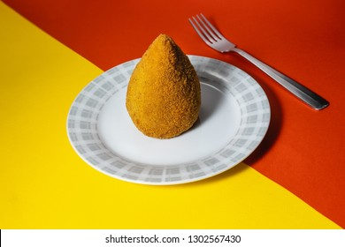 Sicilian Arancino on red and yellow color Sicilian flag