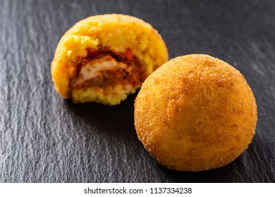 Sicilian Arancino, typical fingers food Sicily, Italy. Fried rice balls, meat-based Italian sauce and peas.