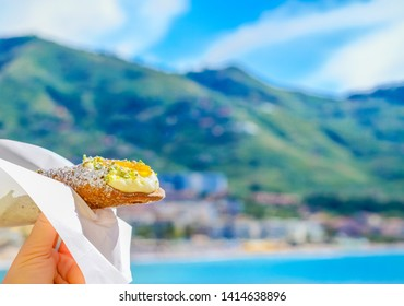 Sicilian cannoli, traditional italian dessert with ricotta cheese. Close up of cannoli on a blurred Sicilian seaside landskape background