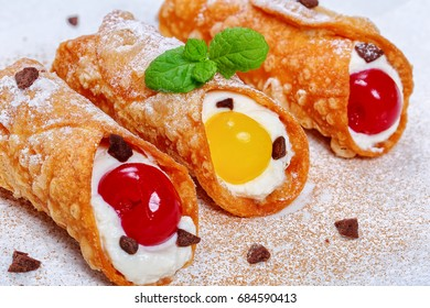 Sicilian Cannoli, traditional italian dessert, filling with ricotta cheese and cocktail cherries on white background sprinkled with chocolate powder and crumbs, authentic classic recipe, close-up