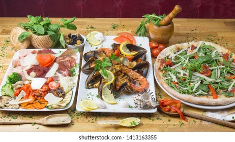 Sicilian food: salad, seafood and pizza, served with decoration on a wooden table.