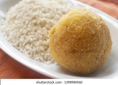 sicilian fried arancino laid on a bed rice