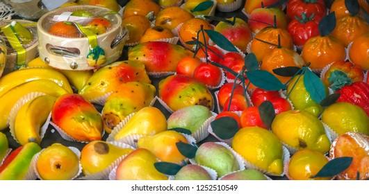 Sicilian marzipan fruits: pear, lemon, orange, banana, papaya, apple on slae in shop