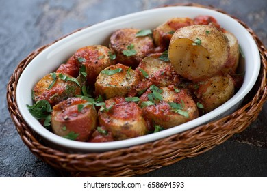 Sicilian style whole baked potato with tomato sauce and chopped parsley, closeup