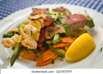 Sicilian taraba - grilled kabob with salmon, gilthead, shrimps and squids on stewed vegetables with a little olive oil and marjoram