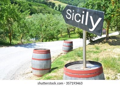 SICILY arrow and wine barrels along rural road