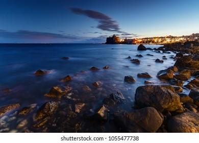 Sicily, Italy: the coast of Acicastello (famous sicilian destination) seen at twilight. Castle illuminated on background.