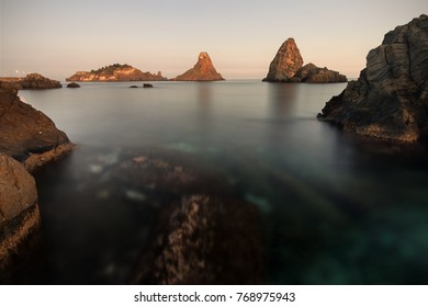 Sicily, Italy: famous Cyclopean Isles and Lachea island at sunset.