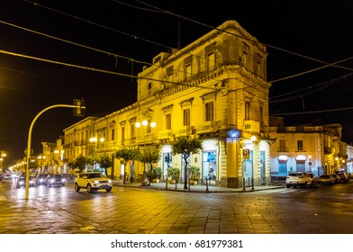 SICILY, ITALY - MARCH 20, 2017: Buildings and shops on the main street, illuminated with yellow light, in the village of Giarre, in the province of Catania