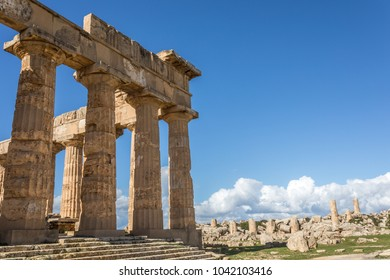 SICILY TRAPANI SELINUNTE GREEK TEMPLE. Series of columns of ancient greek temple, and building ruins, at the archeological site of Selinunte, during a sunny day, with blue sky, clouds and green grass.