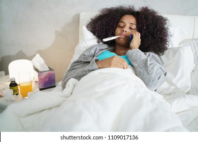Sick african american girl with flu in bedroom at home. Ill young black woman with cold calling doctor by phone, holding a thermometer in her mouth.