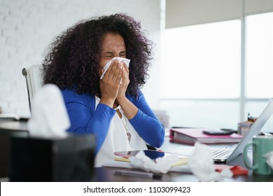 Sick african american girl working from home office. Ill young black woman with cold, sitting at desk with laptop computer and sneezing for allergy.
