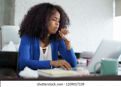 Sick african american girl working from home office. Ill young black woman with cold, working on laptop computer, coughing and sneezing.