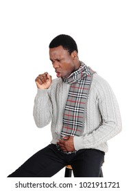 A sick African American man in a gray sweater and scarf sitting on a