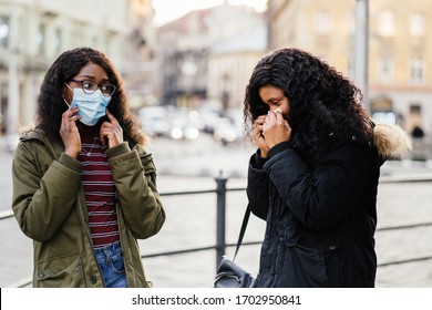 Sick african girl with sneezing at city street, woman without protective mask while spreading flu,cold, Covid-19 or Coronavirus, bad etiquette, manners for cough, sneeze should cover the mask.