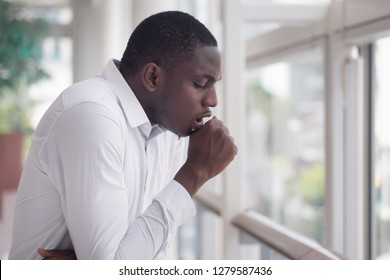 Sick African man coughing; Portrait of ill black man cough due to cold, flu, allergy, polluted air, fine dust, tuberculosis; air pollution, virus, lung cancer, emphysema concept; African man model