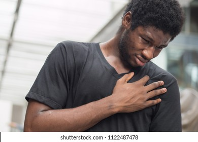sick african man with heart attack or chest pain; portrait of african man suffering from heart attack, chest pain, health care concept; young adult african man or black man model