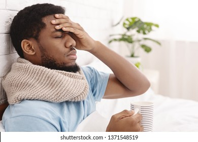 Sick african-american man having fever, drinking hot healing tea and touching forehead in bed, copy space