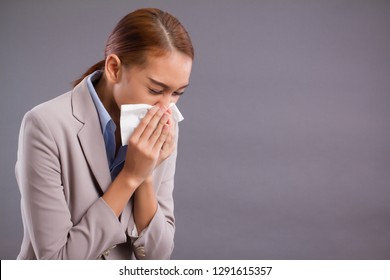 sick allergic woman sneezing; ill asian woman with dust or pollen allergy, polluted air, runny nose, cold, flu, illness; health care or air pollution concept; young adult tan skin asian woman model