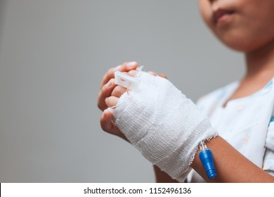 Sick asian child girl hand who have saline intravenous (iv) drip bandage is praying with folded her hand in the hospital
