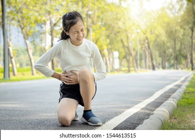 Sick asian child girl holding her hands on belly having stomach painful in the right side attack of appendicitis,female teenage suffer from stomachache feel acute pain,appendicitis symptoms at park