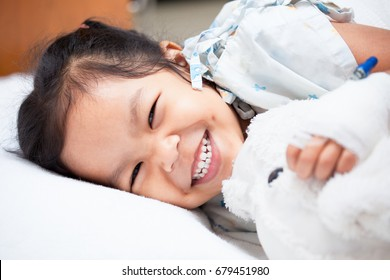 Sick asian child girl is lay down on the bed and smiling when she feel better in the hospital