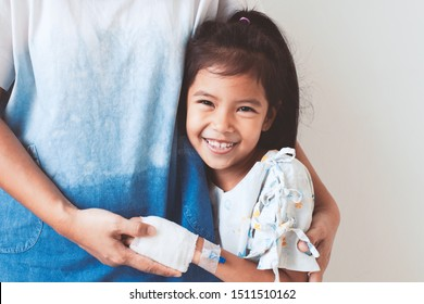 Sick asian child girl who have IV solution bandaged smiling and  hugging her mother with love in the hospital