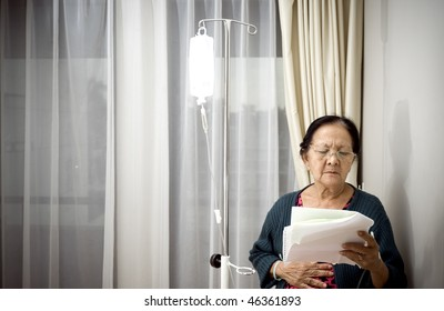 sick asian elderly woman during medication and inpatient treatment at the hospital. worried reading laboratory test result