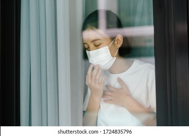 Sick asian female of corona virus looking through the window and wearing mask protection and recovery from the illness in home. Quarantine. Patient isolated to prevent infection. Coronavirus concept.