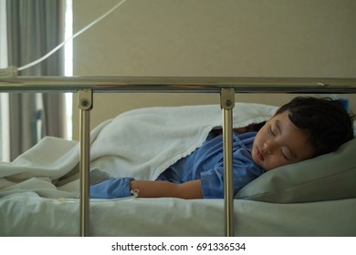 Sick Asian kid boy 2 years old lying sick in hospital bed. dim light, selective focus.