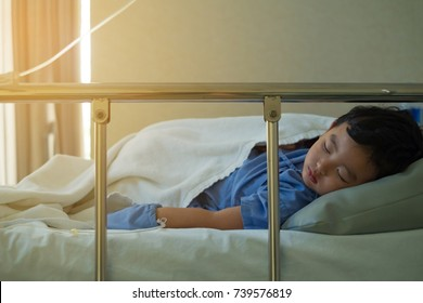 Sick Asian kid boy 2 years old lying sick in hospital bed. dim light, selective focus. soft tone.