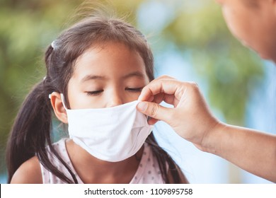 Sick asian little child girl wear protection mask and mother help to close her nose