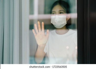 Sick asian male of corona virus looking through the window and wearing mask protection and recovery from the illness in home. Quarantine. Patient isolated to prevent infection.