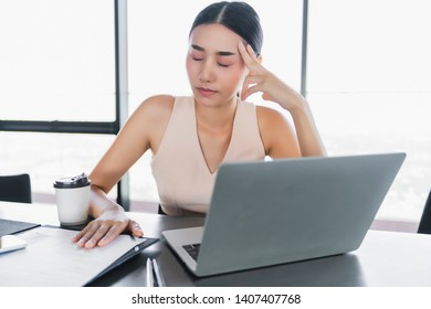 sick asian office woman bad health with office syndrome while working with laptop in office