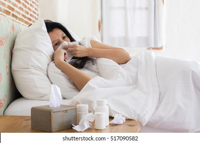Sick asian woman blowing her nose while in bed and medicine in foreground.