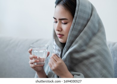 Sick asian woman eating pills with a glass of water in hand with tired face. Healthy, medicine taking, chemical, illness, sickness, health care, pharmacy, coronavirus, covid-19 prevent concept.
