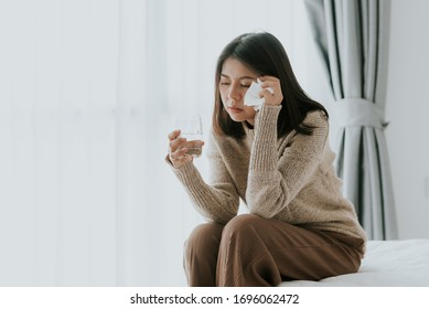 Sick Asian woman feeling headache from flu and cold holding a glass of water at home